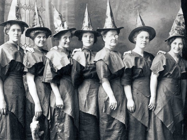 A 'coven of witches' line up for a Halloween portrait dressed in festive witch's hats and improvised costumes, ca.1910, United States. (Photo by Transcendental Graphics/Getty Images)